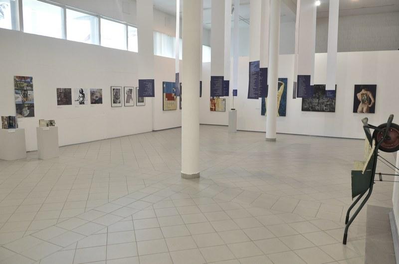 A Nyílt, ti, tok című tárlat részlete - azok munkáival, akiknek Vass Tibor korábban kiállítását nyitotta meg; a szalagokon versek az új kötetből (Fotó: Kiss Ágoston)